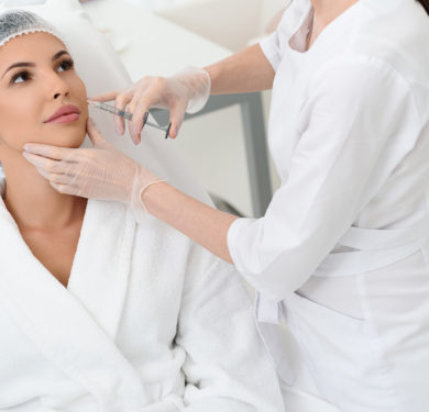 Professional doctor is injecting botox rejuvenated liquid into female face. Young woman is sitting and looking at beautician with trust